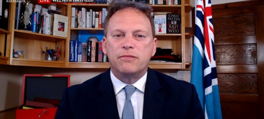 Grant Shapps with red box and civil air ensign military flag.